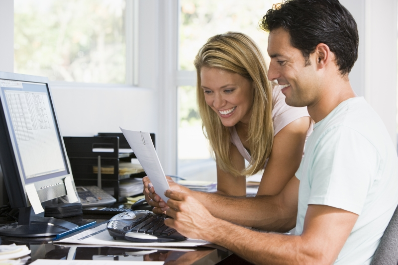 2130741-couple-in-home-office-with-computer-and-paperwork-smiling